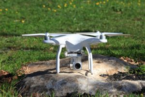 Drone equipped with high resolution 4K video camera placed on a green field ready for take off